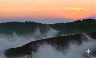 Sbuffi di nebbia tra le montagne al tramonto